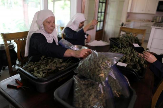 "California ""weed nun"" Christine Meeusen, who goes by the name Sister Kate, and India Delgado, who goes by the name Sister Eevee, trim hemp in the kitchen at Sisters of the Valley near Merced"